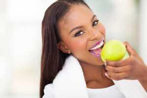 african american woman eating apple