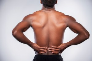 man holding lower back appearing to be in pain, backache