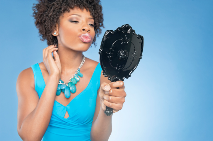 woman puckering lips in mirror