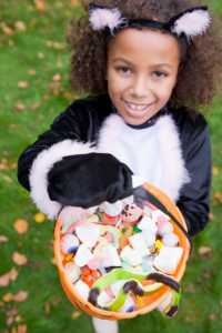 young african american girl holding halloween candy in a jack o latern