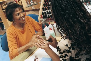 smiling african american woman having her nails done in a nail salon
