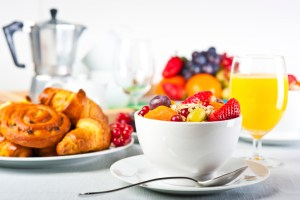 bowl of fruit, toast, juice and cereal