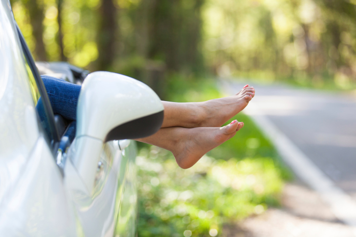 woman feet hanging out car