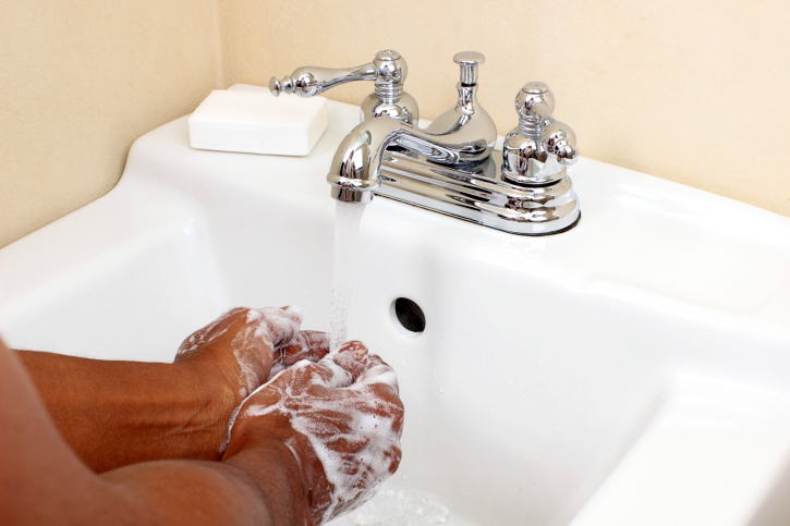 Black person washing with soap and water