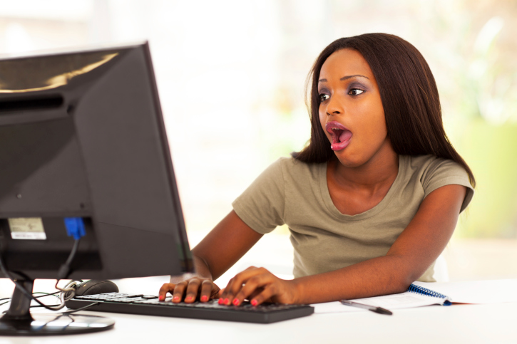 young woman on computer shocked