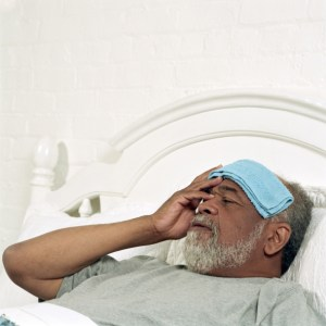 older man with wet towel on his head