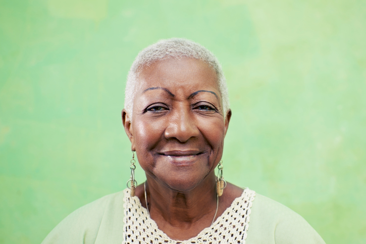 older woman smiling green background