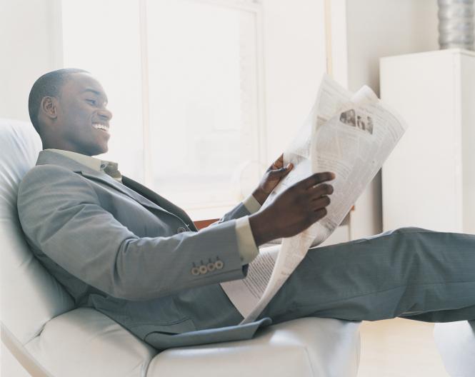 man relaxing reading newspaper