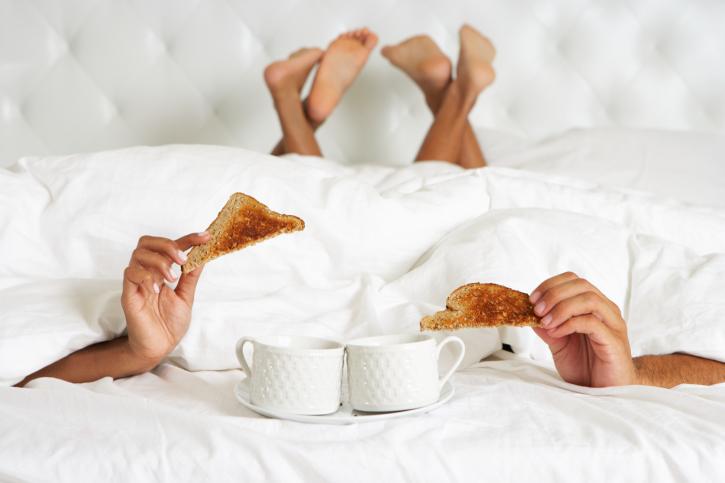 couple hiding breakfast in bed