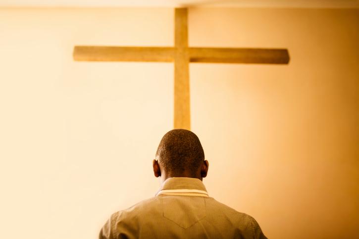 man in front of cross