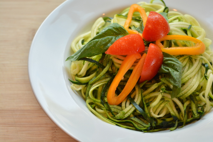 Raw zucchini spaghetti with basil, tomato and yellow pepper