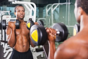 man lifting weights in a mirror