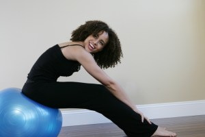 smiling woman sitting on workout ball