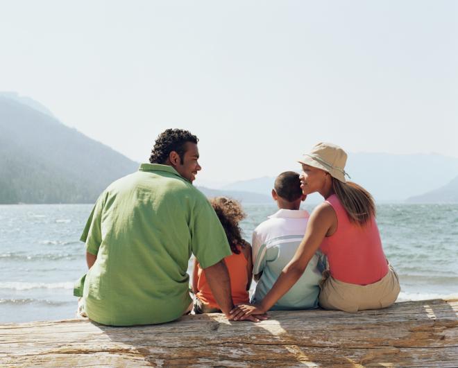 family sitting on lake