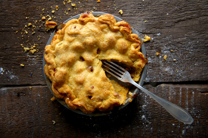 Apple Pie on Rustic Wooden Background with Fork and Crumbs