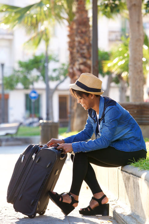 African American black woman sitting outside with suitcase