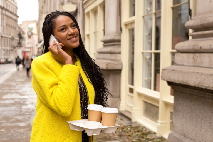 African American Black woman talking on cell phone outside carrying coffee
