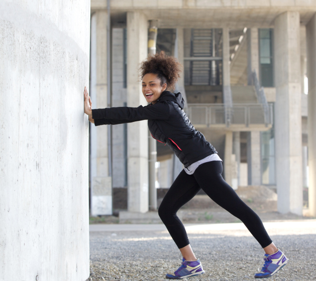 African American Black woman stretching exercise outdoors leggings