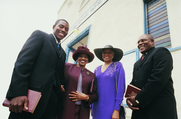 Portrait of Four Smiling Black African American People Standing Outside a Church With Their Bibles