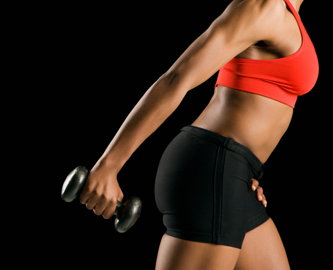 side profile African American woman lifting dumbbell weight