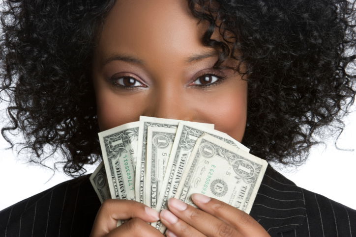 African American Black woman holding money up to her face
