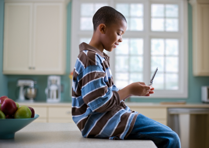 young African American boy sitting in kitchen looking at cell phone
