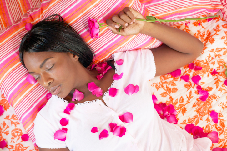 High angle view of a young woman lying on a bed with roses petals on her
