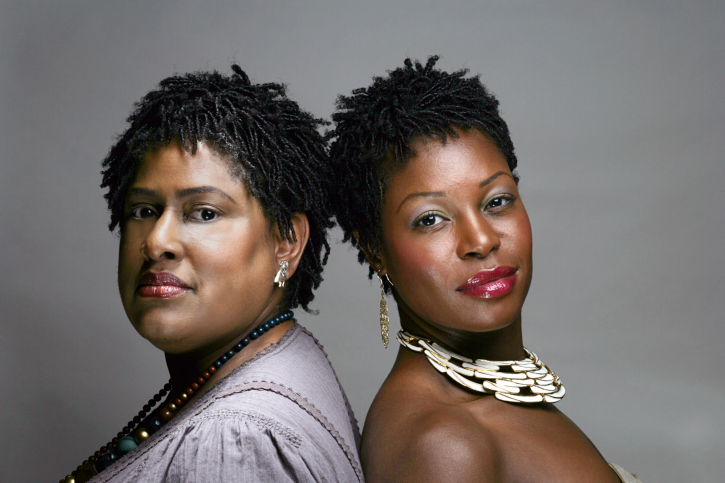 two black women standing back to back