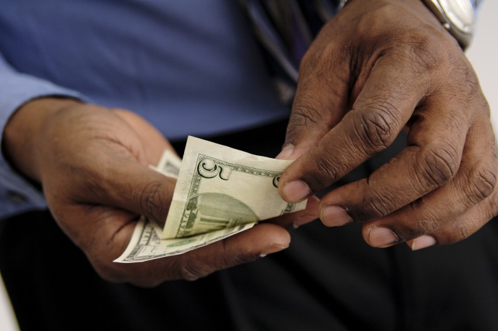 Older African American man counting money