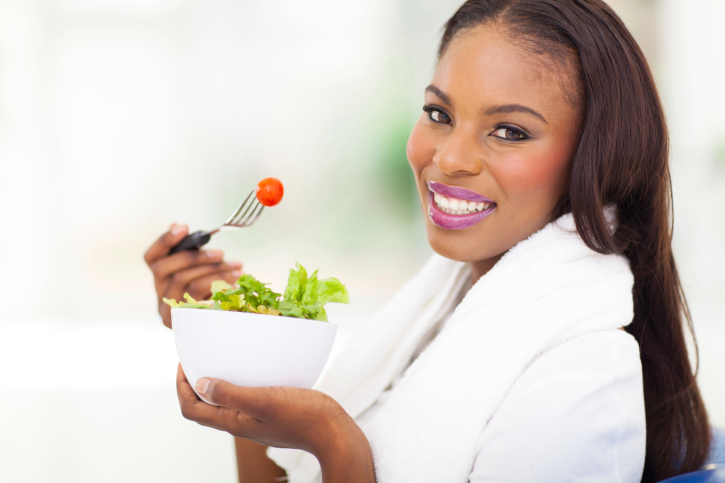 African American woman with long hair eating salad