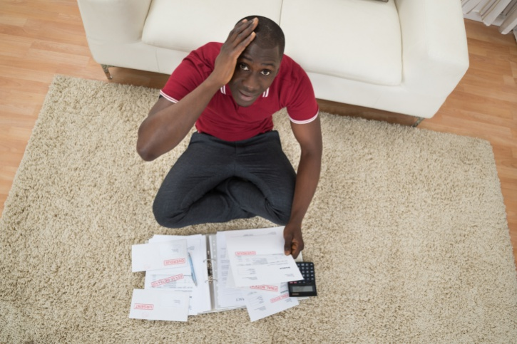 African American man worried looking at bills