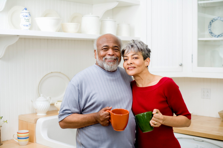 African American senior couple in kitchen hugging with coffee mugs
