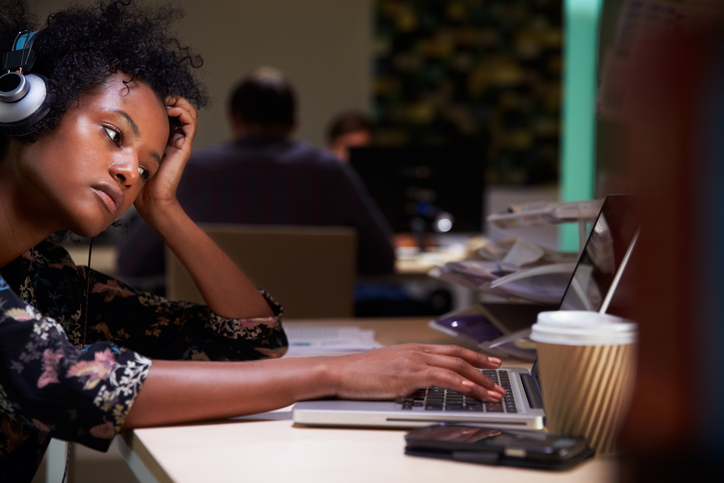 African American woman working late in office on laptop