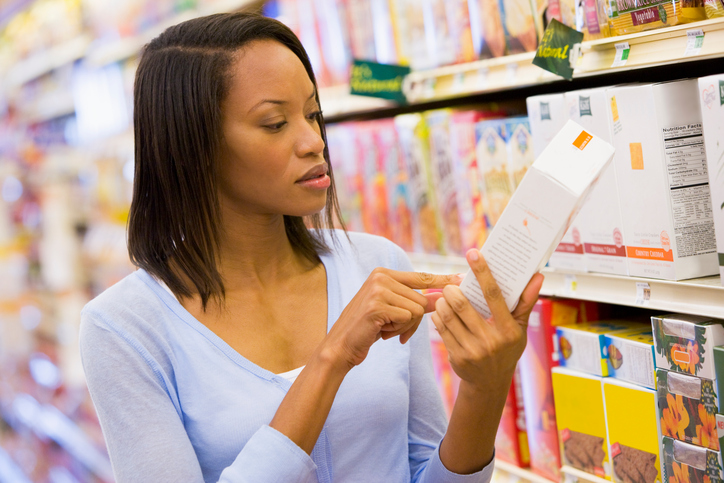 Woman reading label in grocery store