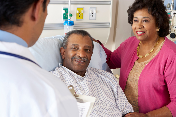 African American senior couple talking to doctor in hospital