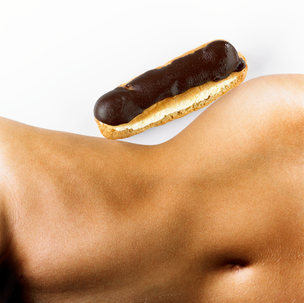 Woman with chocolate eclair 'balanced' on hip, mid section