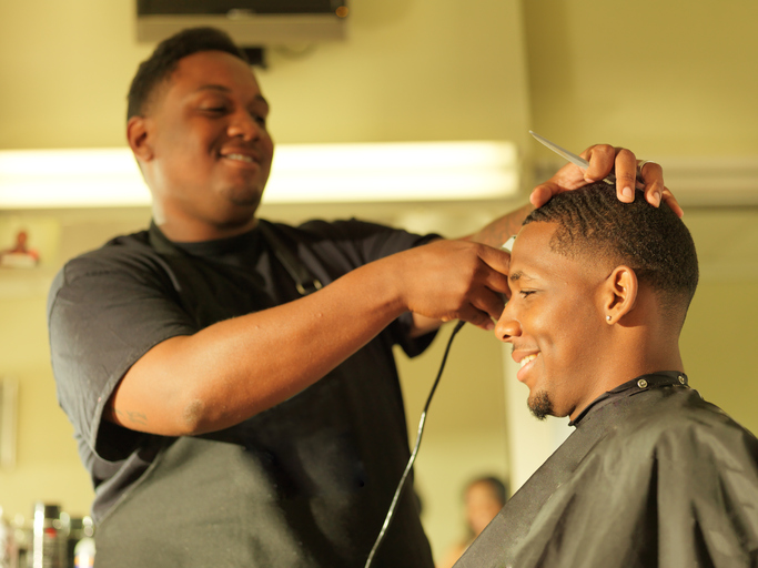 African American man getting hair cut at barbershop