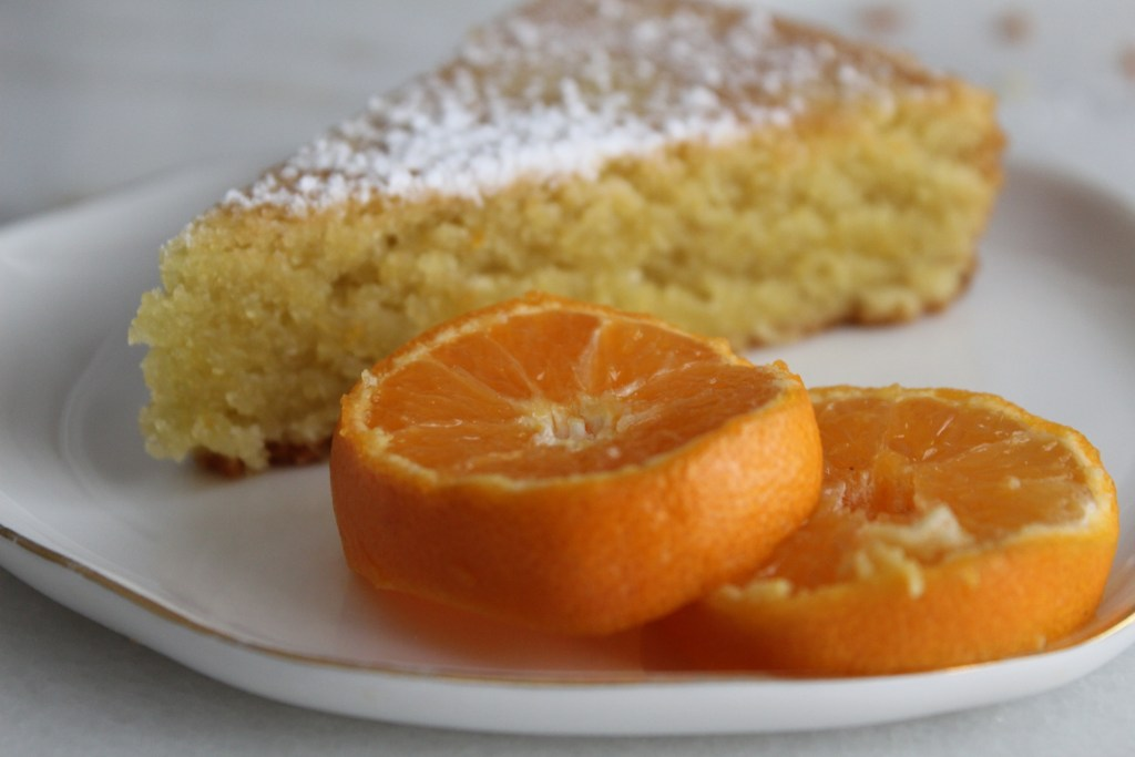 Slice of Almond Flour Olive Oil Cake with orange slices as garnish