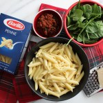 Box of Pasta, Bowl of Pasta, Bowl of Sauce, Cheese and Cheese Grater and Spinach