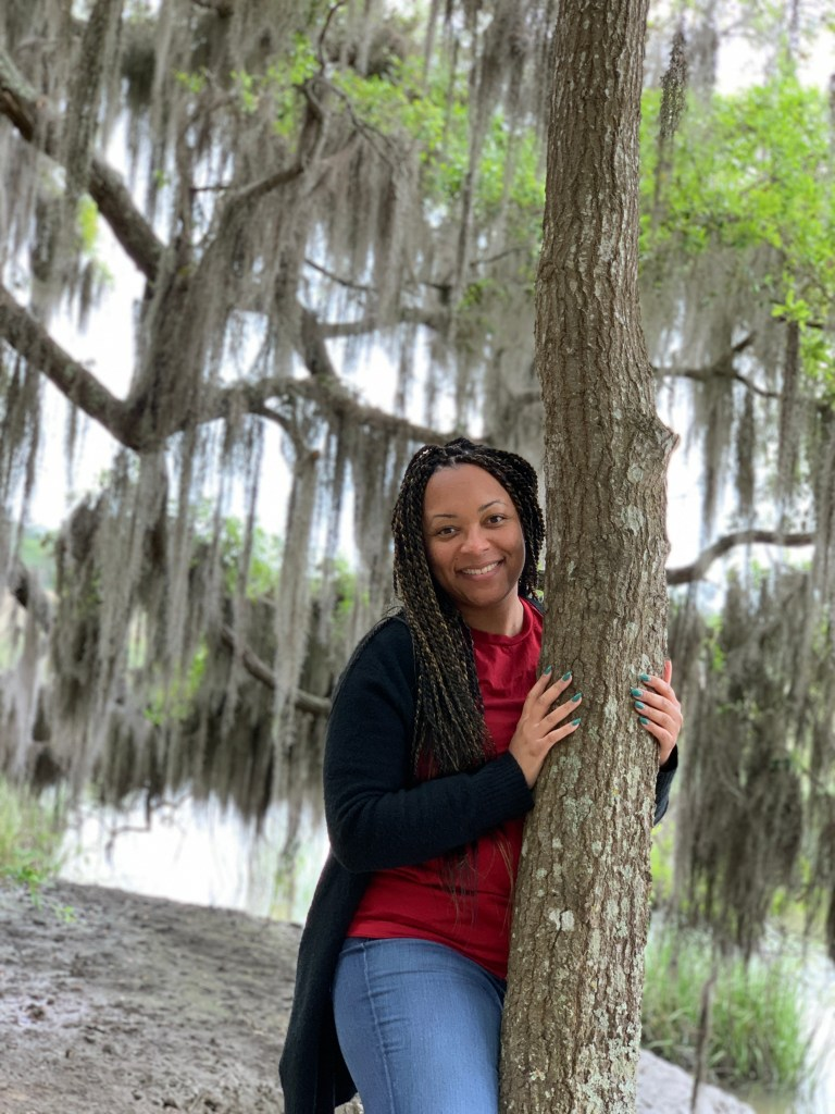 Woman Standing behind Spanish Moss Trees