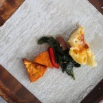 Egg roll wrapper topped with sweet potato, red pepper, collard greens and mac and cheese