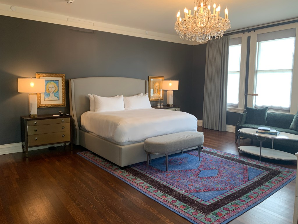 Hotel room with chandler, large bed in the center, with rug and couch and table on the right