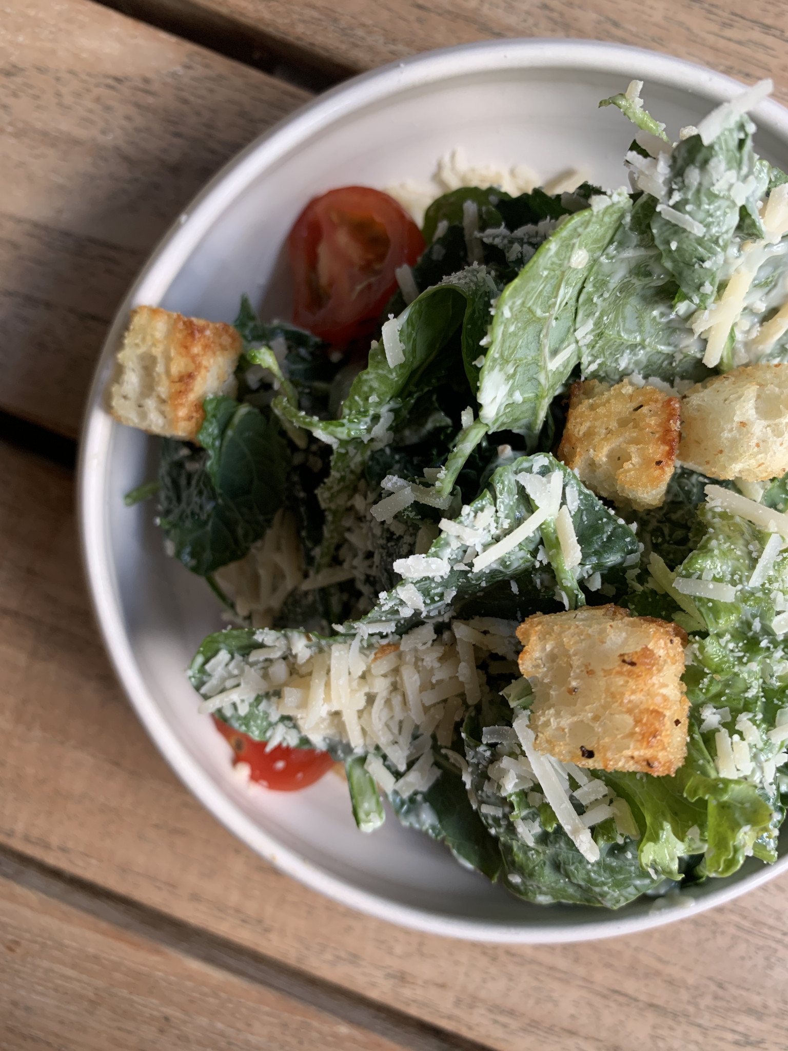 A Caesar salad on a white plate with large croutons and tomatoes