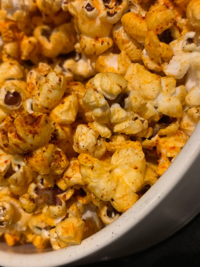 White bowl of flavored popcorn that is orange with red seasoning