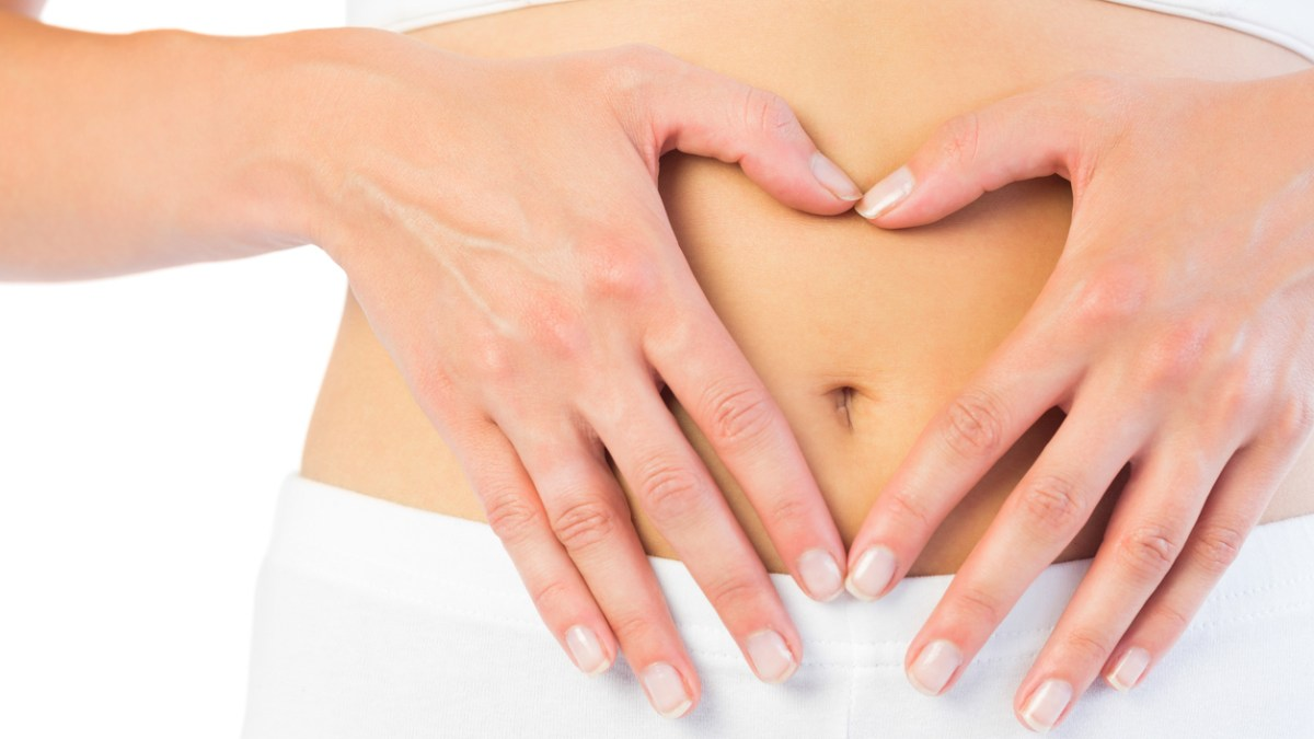 Close up picture of fit woman holding her stomach on white background