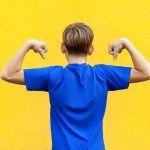back of boy flexing arms on yellow background