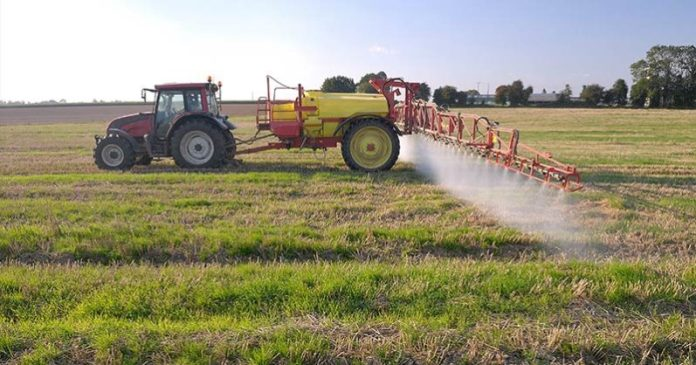 Image of a tractor spraying crops with herbicide