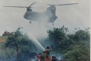 Image of a u.s. helicopter in Viet Nam, with soldiers spraying Agent Orange