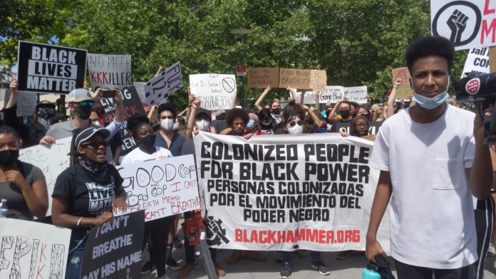colonized people protesting signs up