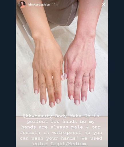 Kim Kardashian's hands -- one tan with makeup, the other one pale and pink